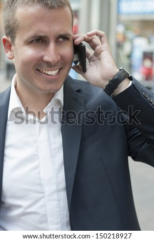 Businessman talking on a mobile phone, on street - stock photo