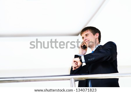 Businessman talking on cell phone and looking at his watch - stock photo