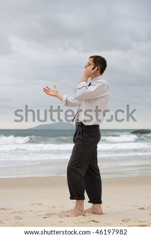 Businessman talking on cell phone on a beach while gesturing with his hand - stock photo