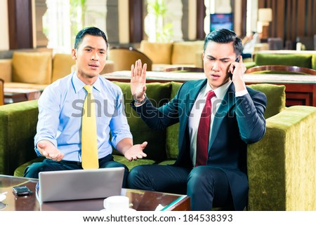 Businessman talking on cell phone while having a meeting - stock photo