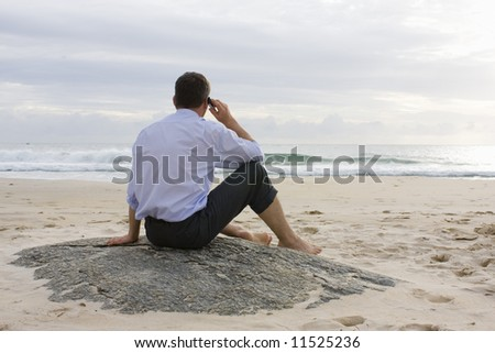 Businessman talking on cell phone while sitting on a beach - stock photo
