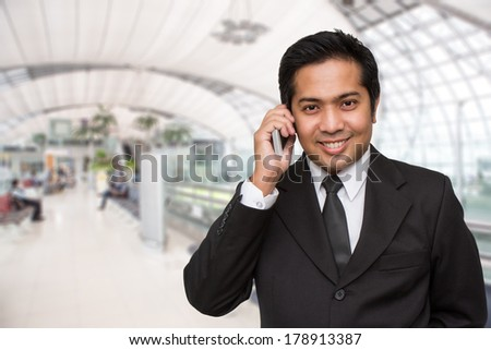 Businessman talking on cellphone at airport - stock photo