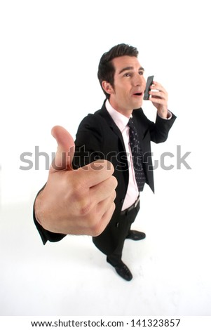Businessman talking on his mobile phone and giving the thumb's up - stock photo