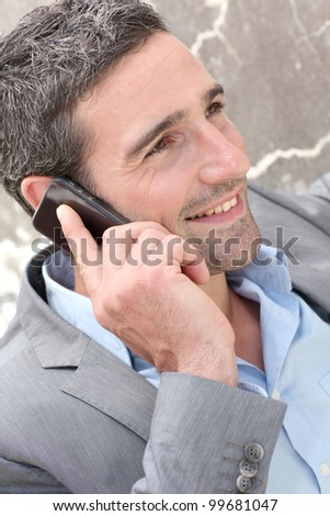 Businessman talking on mobile phone against wall - stock photo