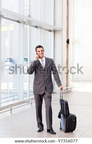 businessman talking on mobile phone at airport - stock photo