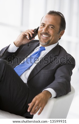 Businessman talking on mobile phone in lobby - stock photo
