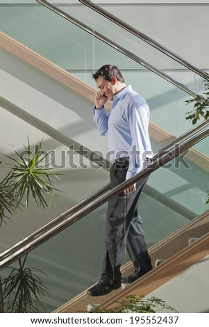 Businessman talking on mobile phone while walking down stairs - stock photo