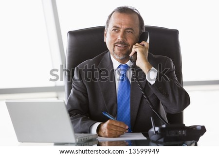 Businessman talking on phone in office - stock photo