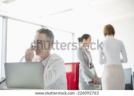 Businessman talking on telephone with colleagues in background at office - stock photo