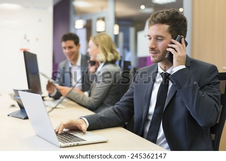 Businessman talking on the mobile phone in modern office - stock photo
