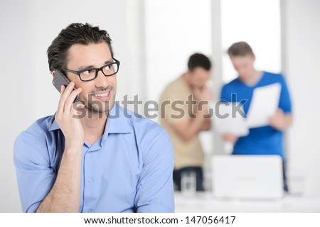 Businessman talking on the phone. Confident young businessman talking at the phone and smiling while colleagues working on the background - stock photo