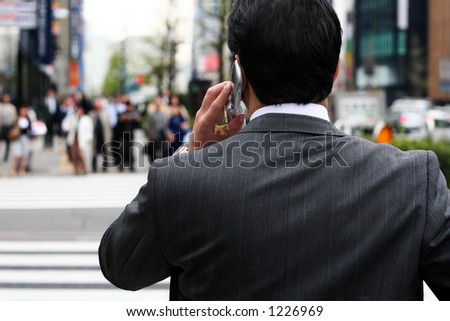 Businessman talking on the phone on the street - stock photo