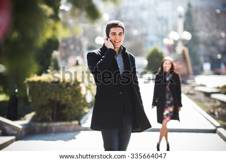 businessman talking on the phone while business woman comes up to him in the park - stock photo