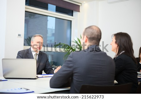 Businessman talking to a couple in a office - stock photo