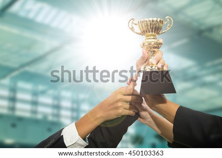 Businessman team holding award trophy for show their victory. - stock photo
