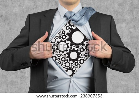 businessman tearing his shirt, cogs and gears - stock photo