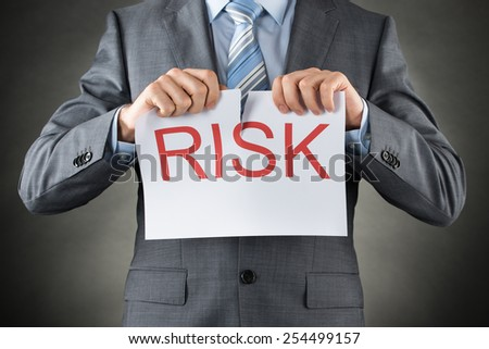 Businessman Tearing The Word Risk On Paper Over Gray Background - stock photo