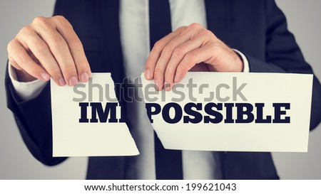Businessman tearing up a sign saying - Impossible - conceptual of successfully overcoming problems and challenges and positive attitude , retro effect faded look. - stock photo