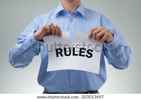 Businessman tearing up the rules or rulebook concept for innovation, creativity or mischief - stock photo