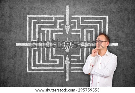 businessman thinking and drawing maze on concrete wall - stock photo