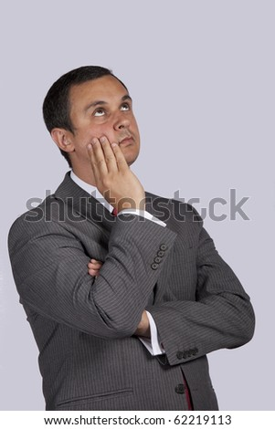businessman thinking and looking to the copy space with a grey background - stock photo