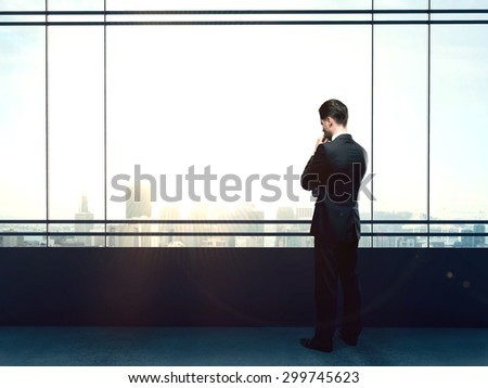 businessman thinking in office and looking to city - stock photo