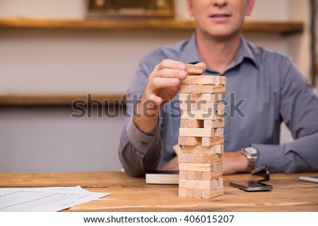 Businessman thinking of expansion with the help of building wooden bricks. Leader gambling placing wooden block on a tower. Business man trying to find a solution to problem with wooden bricks.    - stock photo