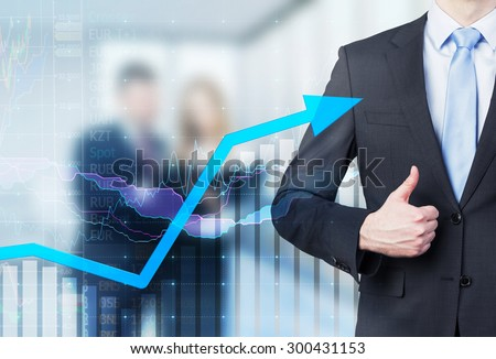 Businessman thumb up and growing arrow. Financial charts and business couple in blur on the background. - stock photo