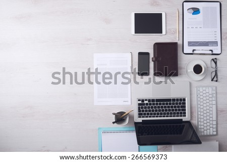 Businessman tidy desktop with laptop, tablet, smartphone, financial reports and various objects, copyspace on the left, top view - stock photo