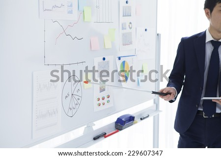 Businessman to presentation using a white board - stock photo