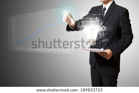 businessman touch graph with lamp of idea - stock photo
