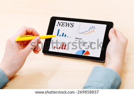 businessman touches by pen of tablet PC with business news on screen at office table - stock photo