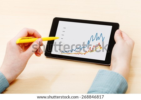 businessman touches by pen of tablet PC with graph on screen at office table - stock photo