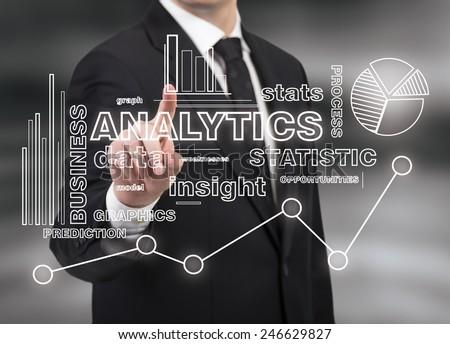 businessman touching analytics symbol on black background - stock photo