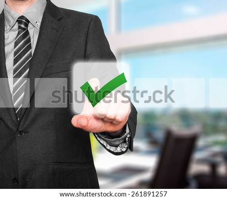 Businessman touching check mark on virtual screen. Isolated on office background. Stock Photo - stock photo