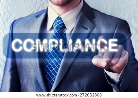 Businessman touching compliance button on virtual screen  - stock photo