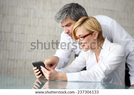 Businessman touching smartphone with businesswoman in office - stock photo