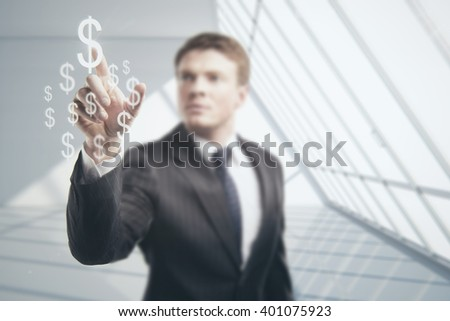 Businessman touching soaring dollar signs on blurry white interior background - stock photo