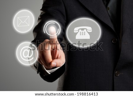 Businessman touching virtual futuristic display with icons for phone, mail and e-mail contact information - stock photo