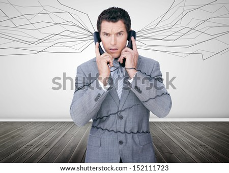 Businessman trapped by telephone wires looking at camera in empty room - stock photo