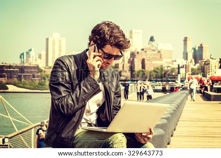 Businessman traveling, working in New York. Wearing sunglasses, a young guy with beard, sitting on bench at harbor, working on laptop computer, talking on phone in same time. Retro filtered look.  - stock photo