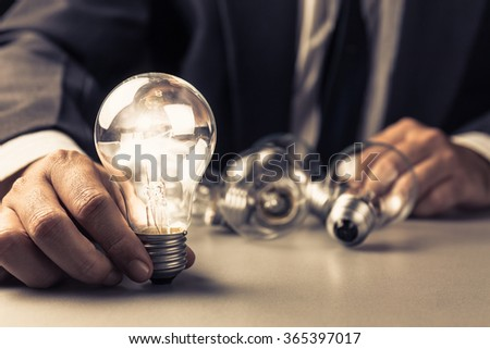 Businessman try to place glowing light bulb on the table - stock photo