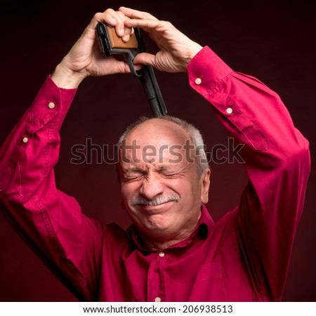 Businessman trying to commit suicide on a dark red background - stock photo