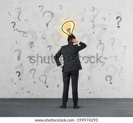 Businessman trying to find a solution. Businessman standing in a question marks and a solution has come - metaphor of light bulb.  - stock photo