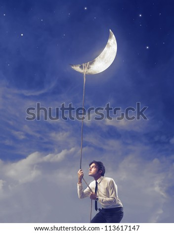 Businessman trying to pull down the moon with a rope - stock photo