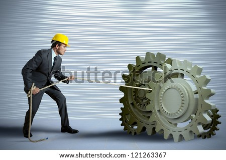 Businessman turning a gear system with rope - stock photo