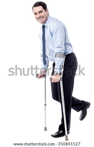 Businessman tying to walk with crutches - stock photo