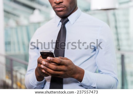 Businessman typing message. Cropped image of young African man in shirt and tie texting on his mobile phone while standing indoors - stock photo