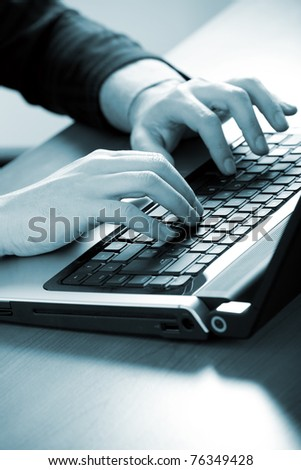 Businessman typing on a laptop - blue toned image - stock photo