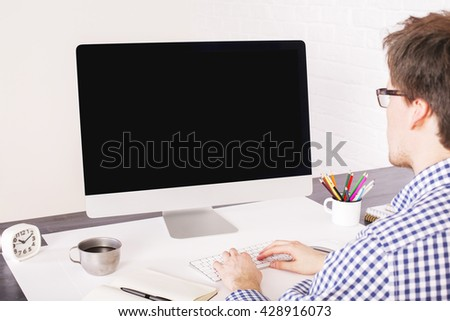 Businessman typing on keyboard placed on office desk with various items and looking at a blank computer screen. Mock up - stock photo